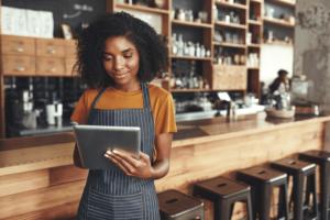 Na imagem, uma jovem pequena empresária, lê em seu tablet a notícia divulgada pela Dr. Fiscal: Receita envia termos de exclusão à devedores do simples nacional
