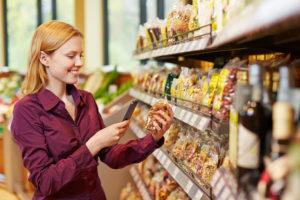 Iniciativa gaúcha, aplicativo Menor Preço terá versão nacional: em loja, jovem consumidora compara o menor preço dos produtos através de seu smartphone, fazendo menção à notícia divulgada